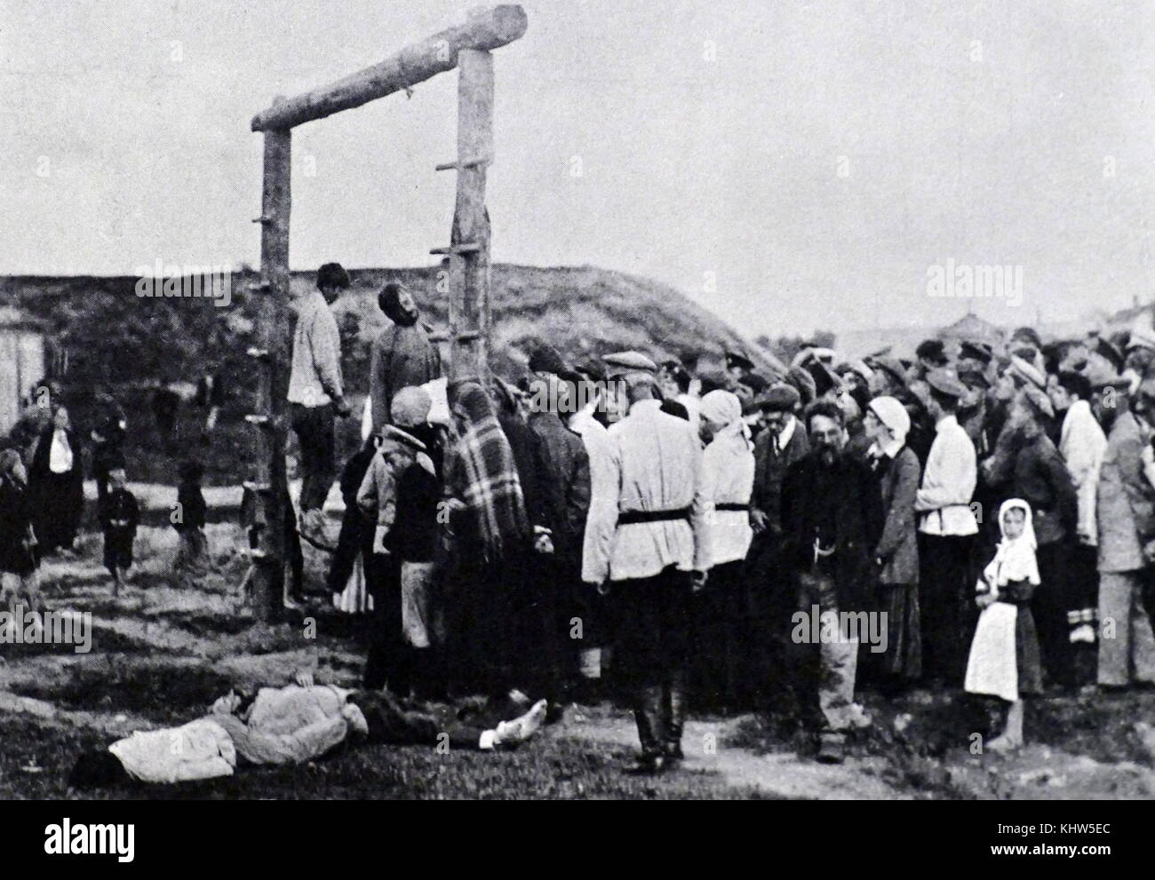 Photograph taken of a White Lynching party. After hanging Bolsheviks, the execution squad invites villagers to take - Stock Image