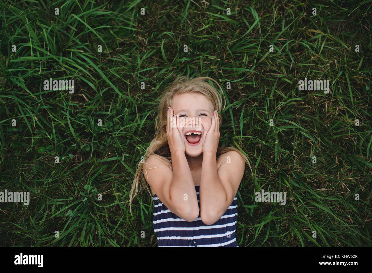 Overhead portrait of girl lying on grass with hands on her cheeks - Stock Image