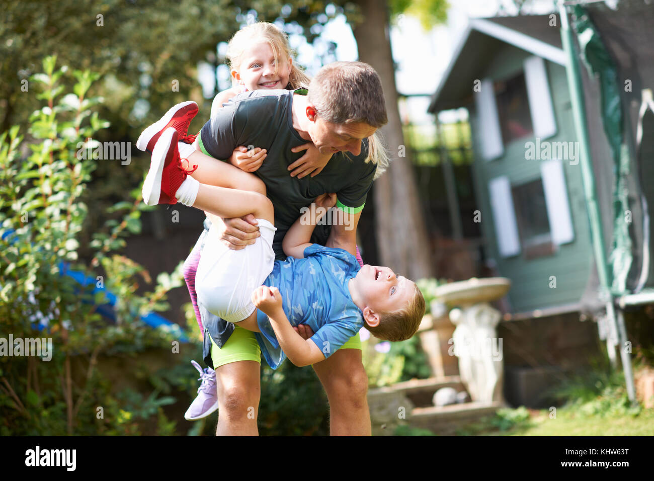 Family playfighting in garden - Stock Image