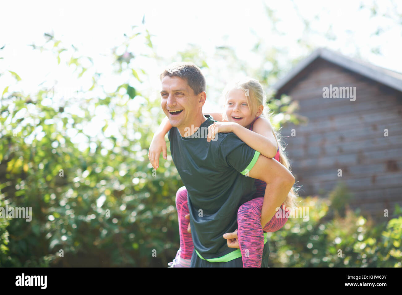 Father giving daughter piggyback in garden - Stock Image