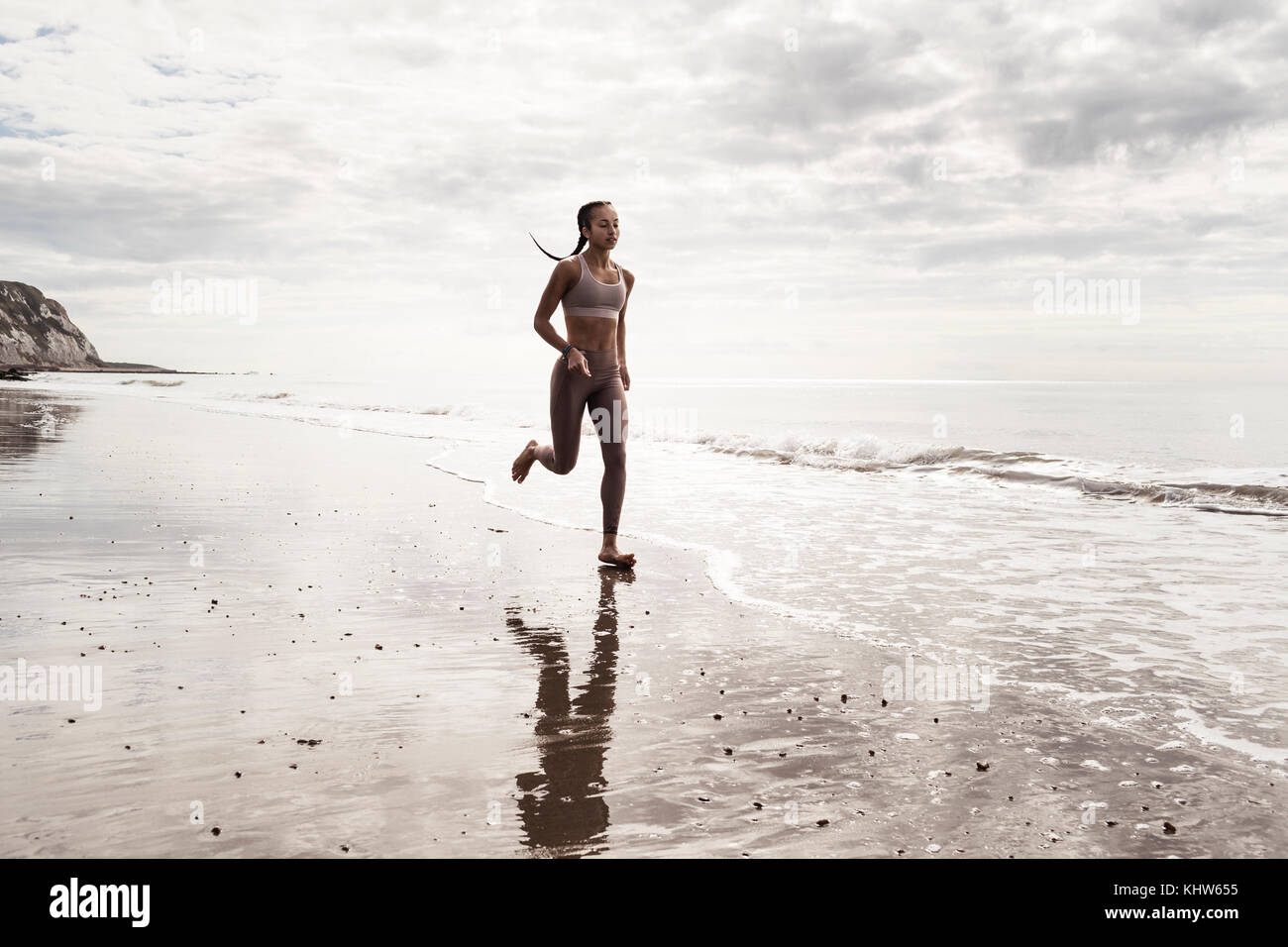 Young female runner running barefoot along water's edge at beach - Stock Image
