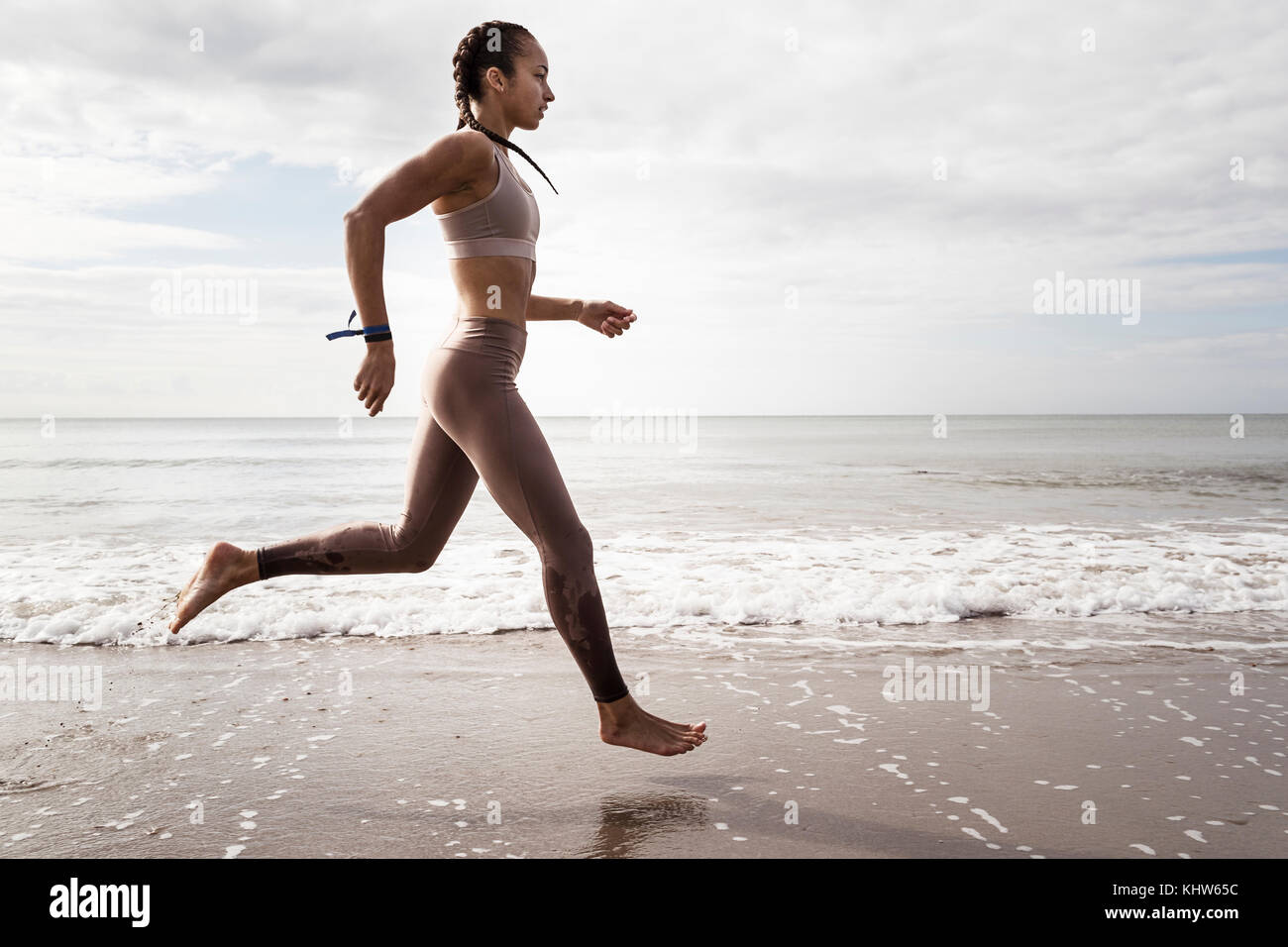 Side view of young female runner running barefoot along water's edge at beach - Stock Image