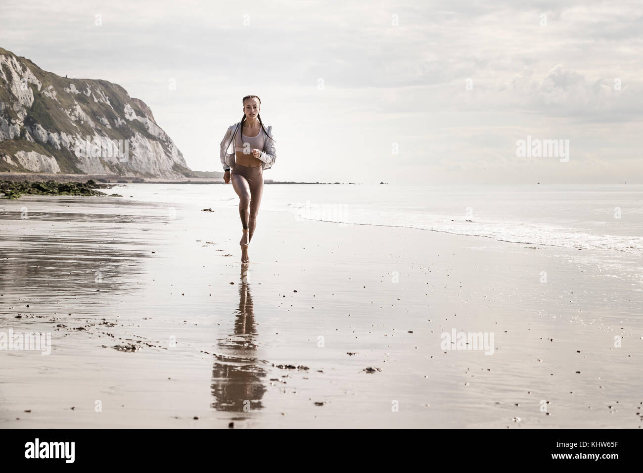 Front view of young female runner running barefoot along beach - Stock Image