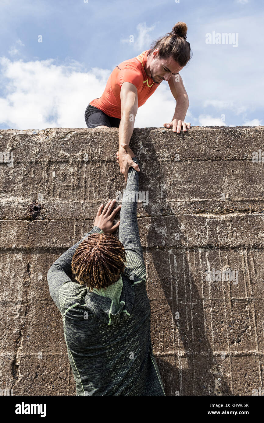 Young male free climber at top of sea wall helping friend climb up - Stock Image