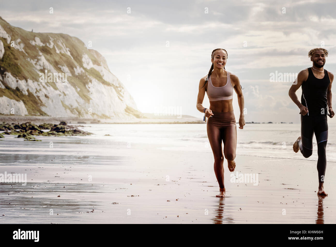 Young male and female runners running barefoot on beach - Stock Image