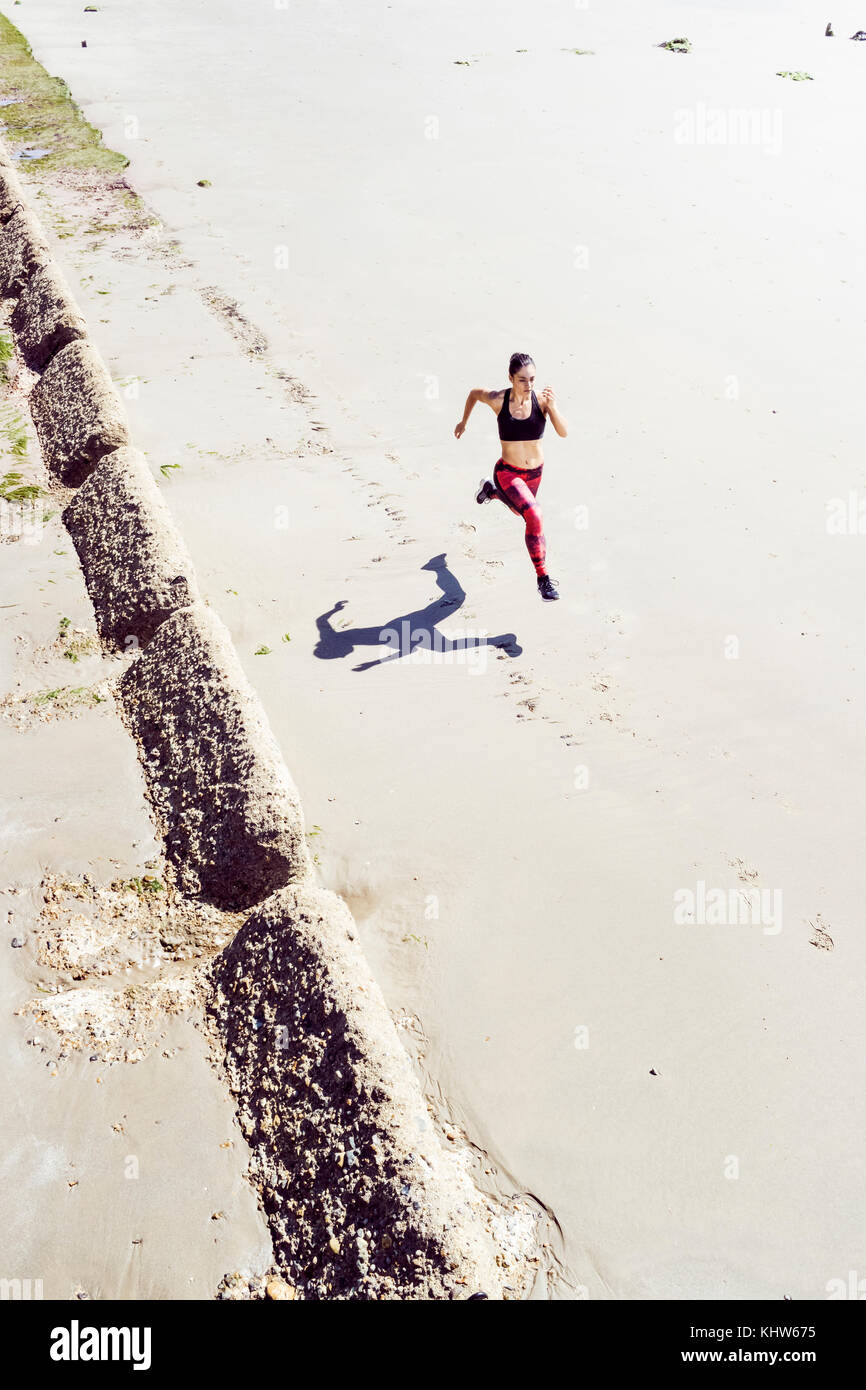 Young woman running along beach, elevated view - Stock Image