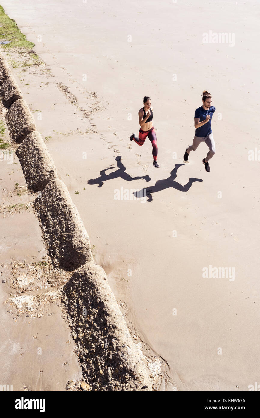 Young man and woman running along beach, elevated view - Stock Image