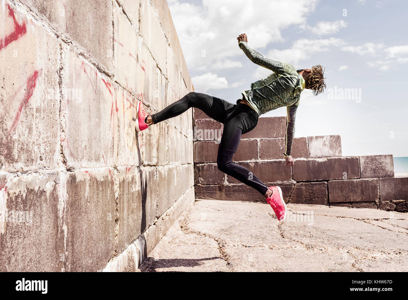 Young man, free running, outdoors, running up side of wall - Stock Image