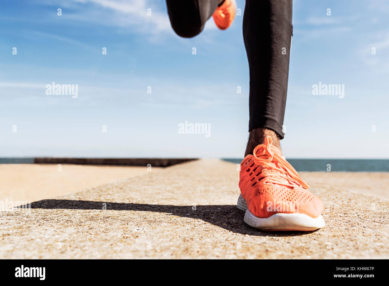 Man running outdoors, low section - Stock Image