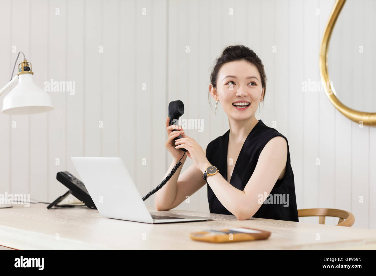 Young woman at desk with telephone handset - Stock Image