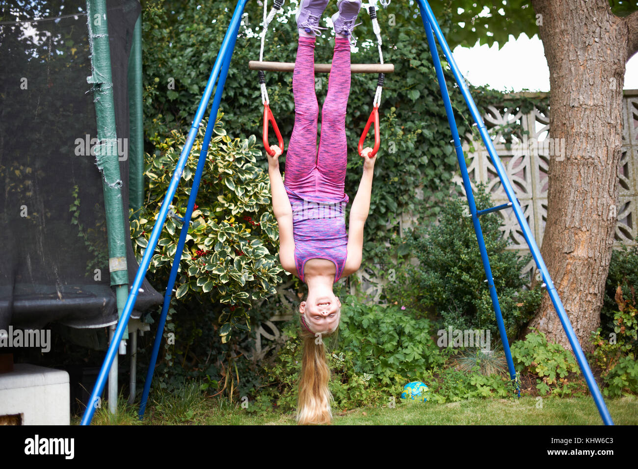 Young girl in garden, hanging upside-down from play frame - Stock Image