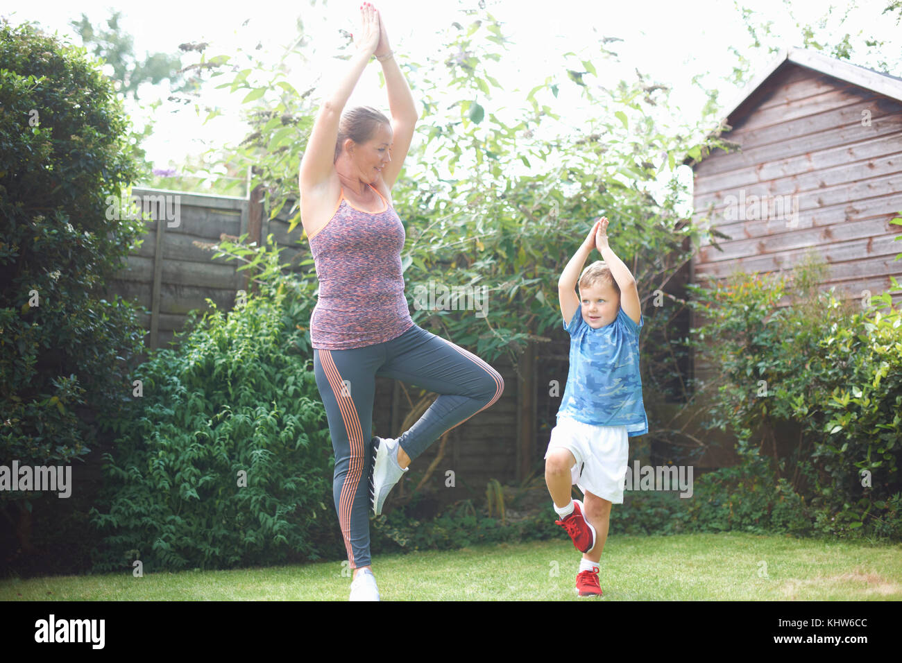 Mother and son exercising in garden, standing in yoga position - Stock Image
