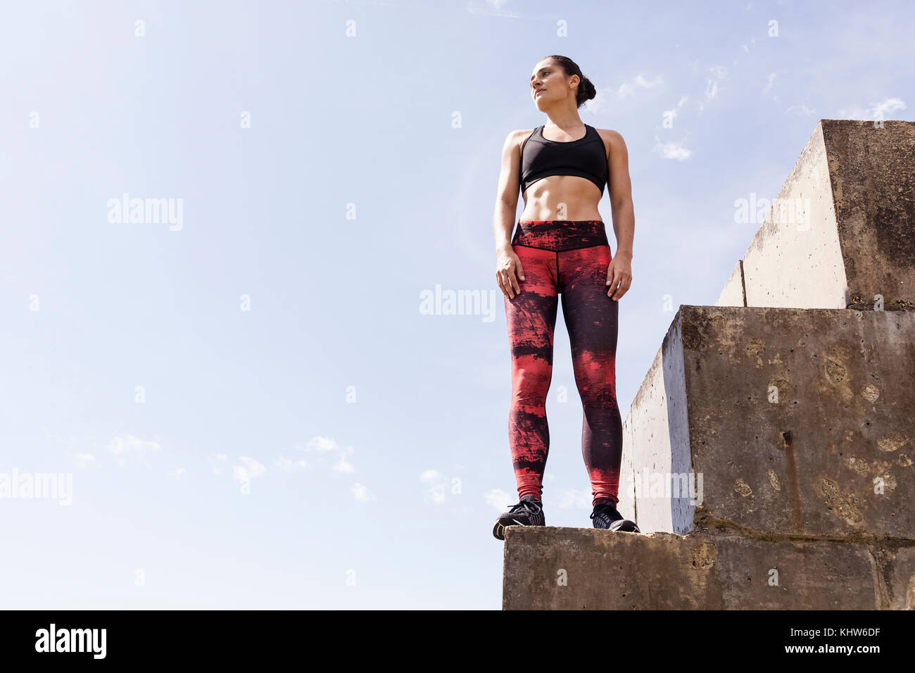 Young female free runner looking out from top of sea wall - Stock Image