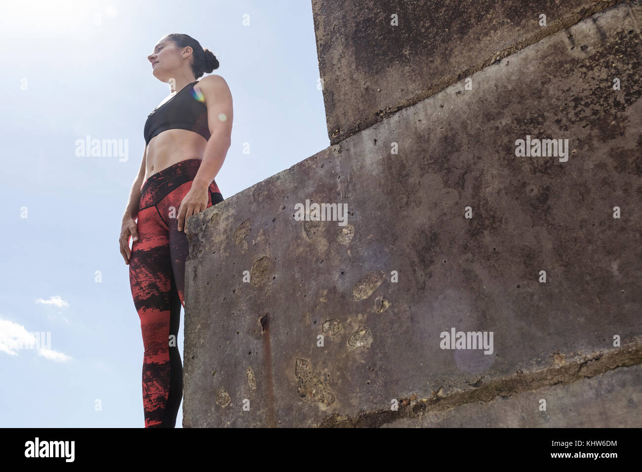 Young female free runner looking out from sea wall - Stock Image