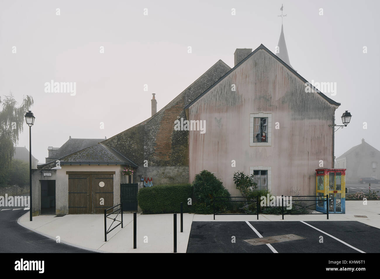 House gable and parking lot in Meigne-le-Vicomte village on misty morning, Loire Valley, France - Stock Image