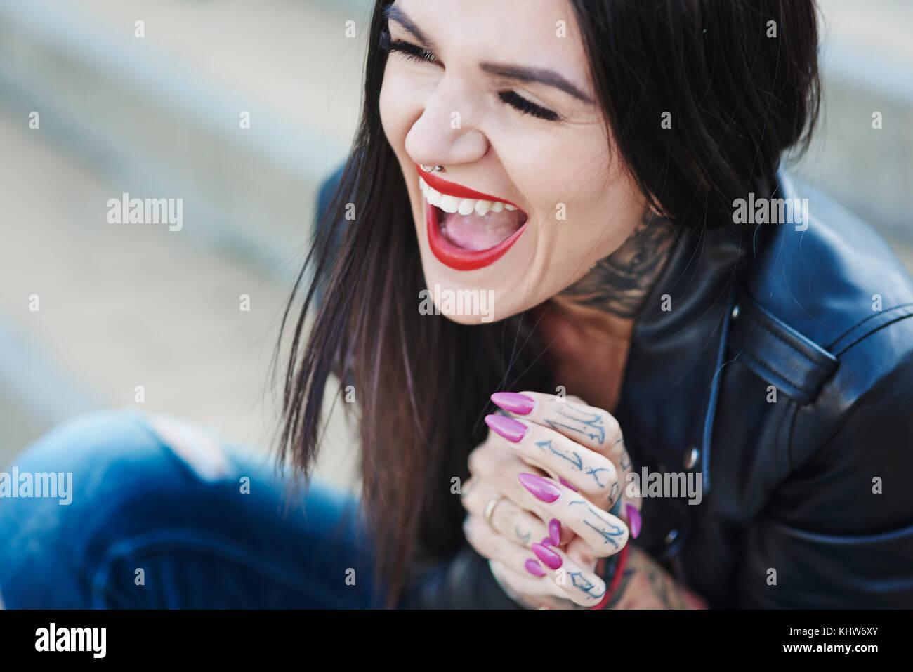 Portrait of young woman laughing, tattoos on neck and hand - Stock Image