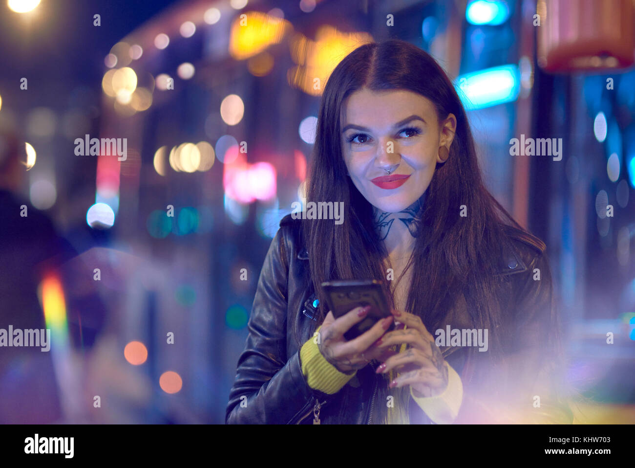 Young woman outdoors at night, holding smartphone, tattoos on hand and neck - Stock Image