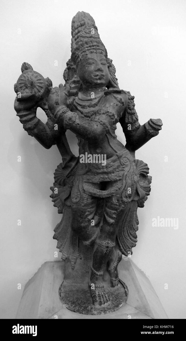Statuette of Krishna playing the flute from South India. Krishna is a major deity in Hinduism. He is the eighth - Stock Image