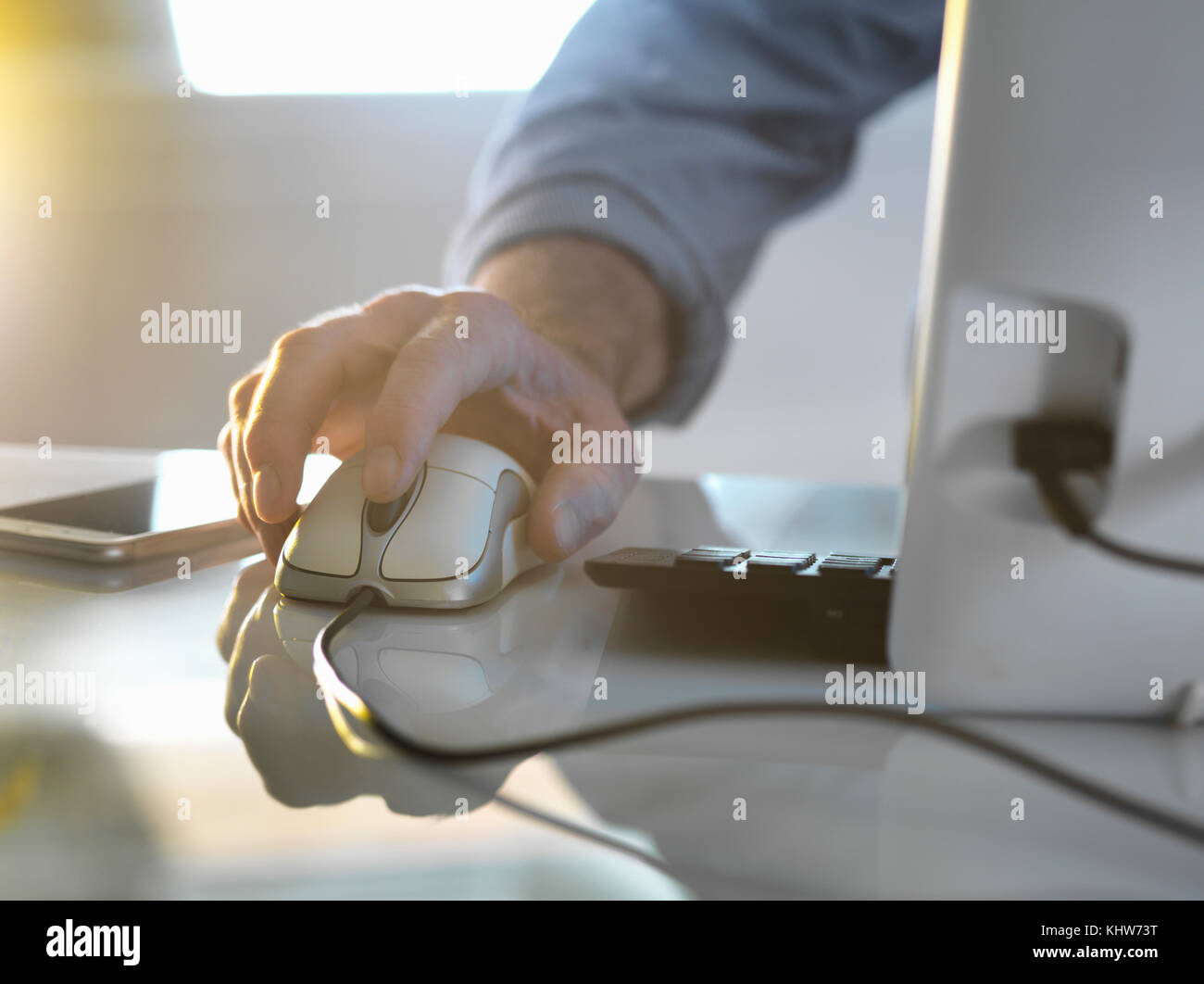 Businessman's hand on a computer mouse working in office - Stock Image