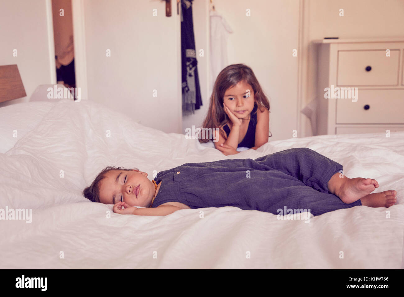 Female toddler, sleeping on bed, older sister watching her sleep - Stock Image
