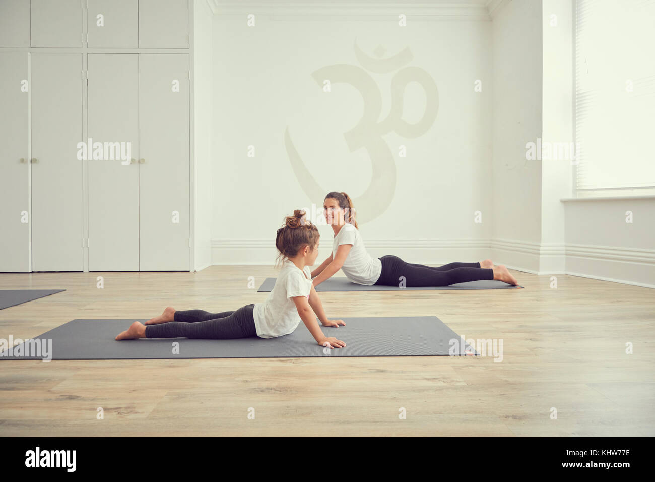 Mother and daughter in yoga studio, in yoga positions - Stock Image