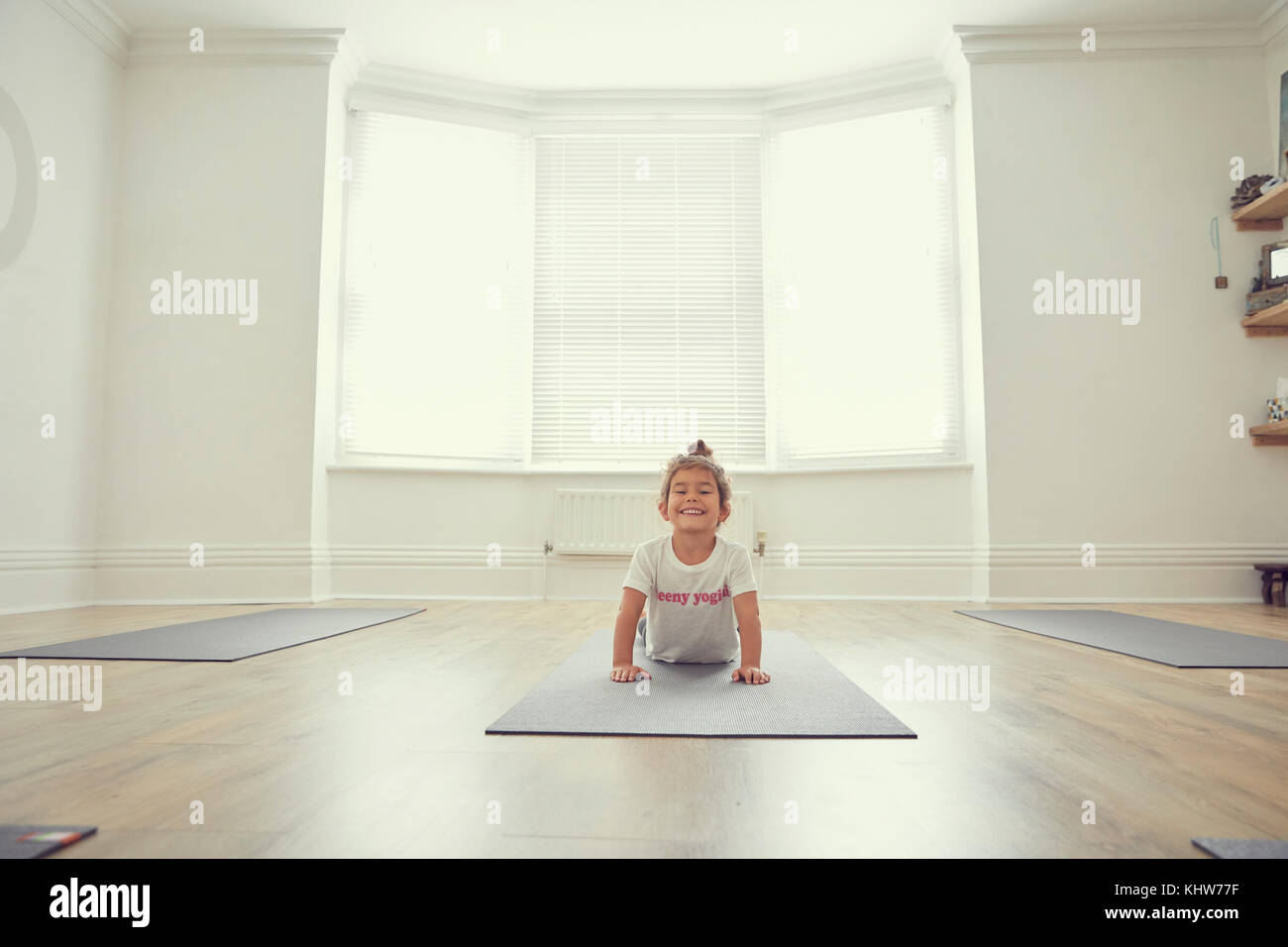 Young girl in yoga studio, in yoga position - Stock Image