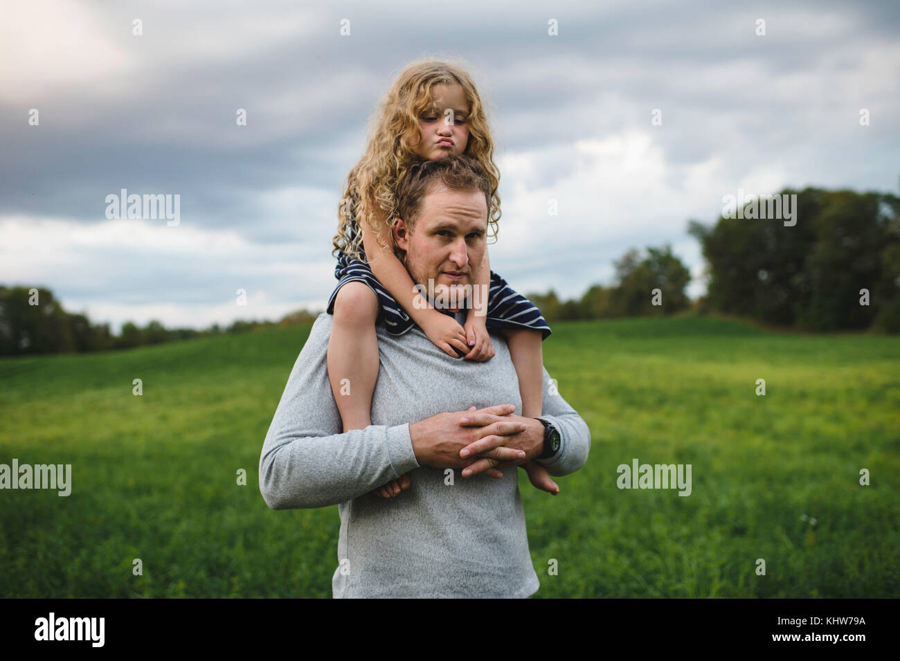 Father and daughter enjoying outdoors on green grassy field - Stock Image