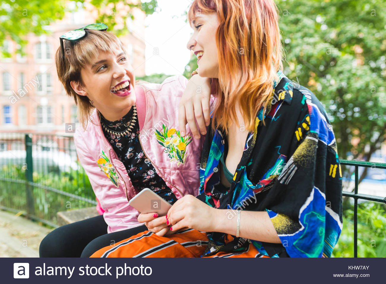 Two retro styled young women laughing in park - Stock Image