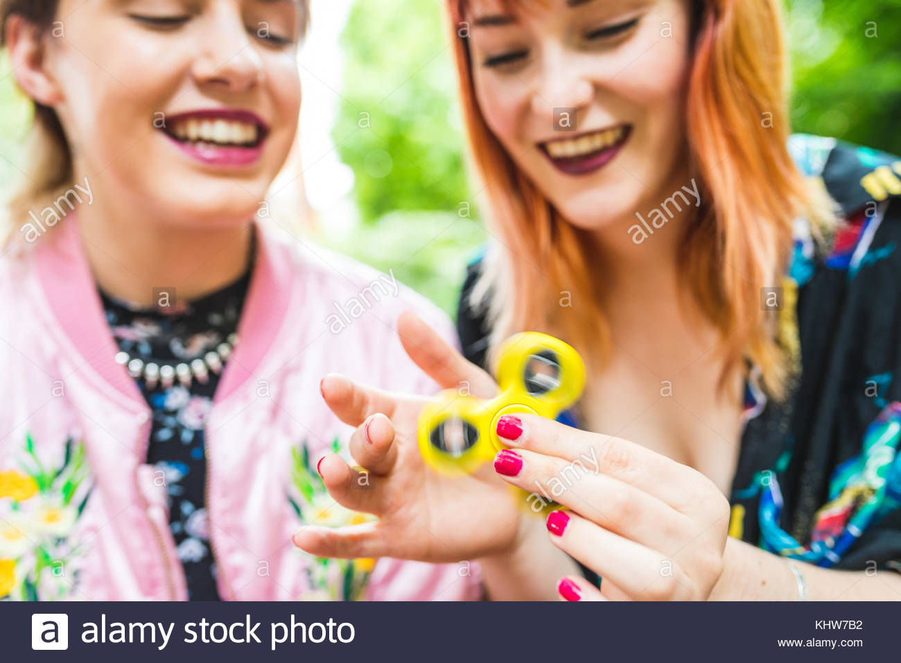 Two retro styled young women playing with fidget spinner in park - Stock Image