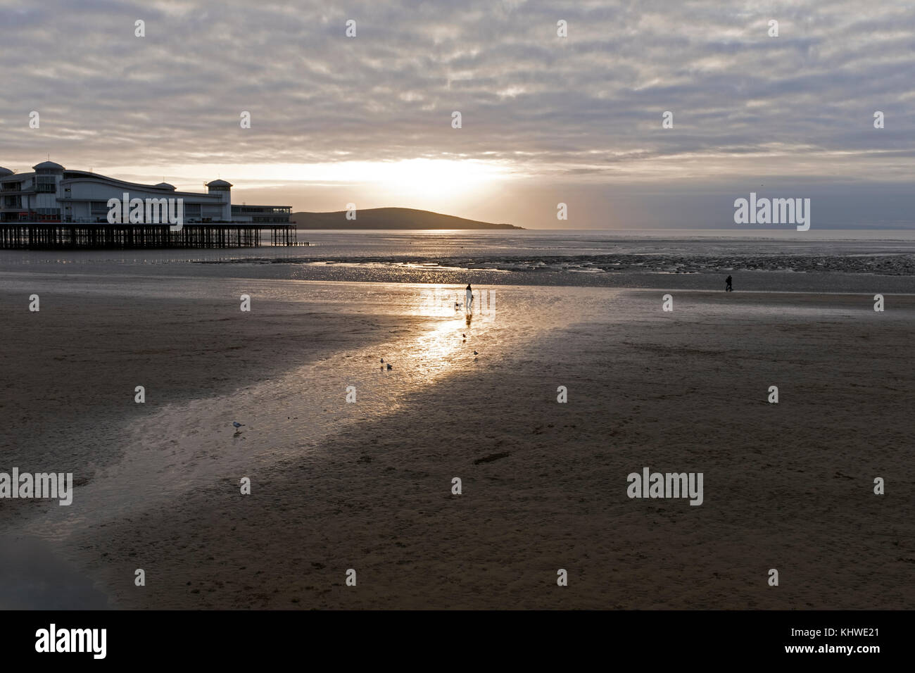 Weston-super-Mare, UK. 19th November, 2017. UK weather: dog walkers on the beach are silhouetted against the setting Stock Photo