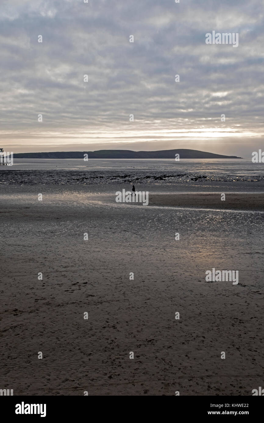 Weston-super-Mare, UK. 19th November, 2017. UK weather: dog walkers on the beach are silhouetted against the setting - Stock Image