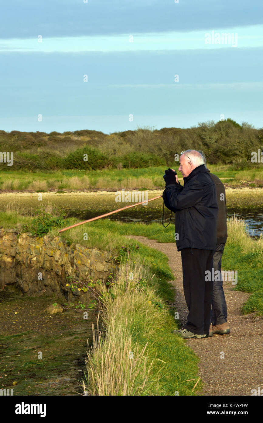 Two elderly or older gentlemen watching birds or twitching and birding on pointing with his stick at some interesting - Stock Image