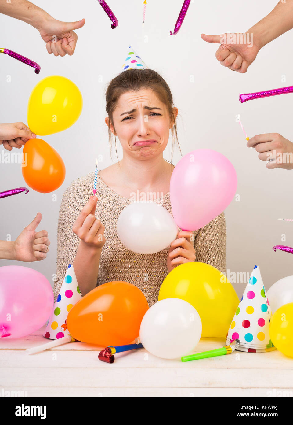 fail, surprise, anniversary concept. young caucasian woman with dark hair is surrounded by balloons and birthday - Stock Image