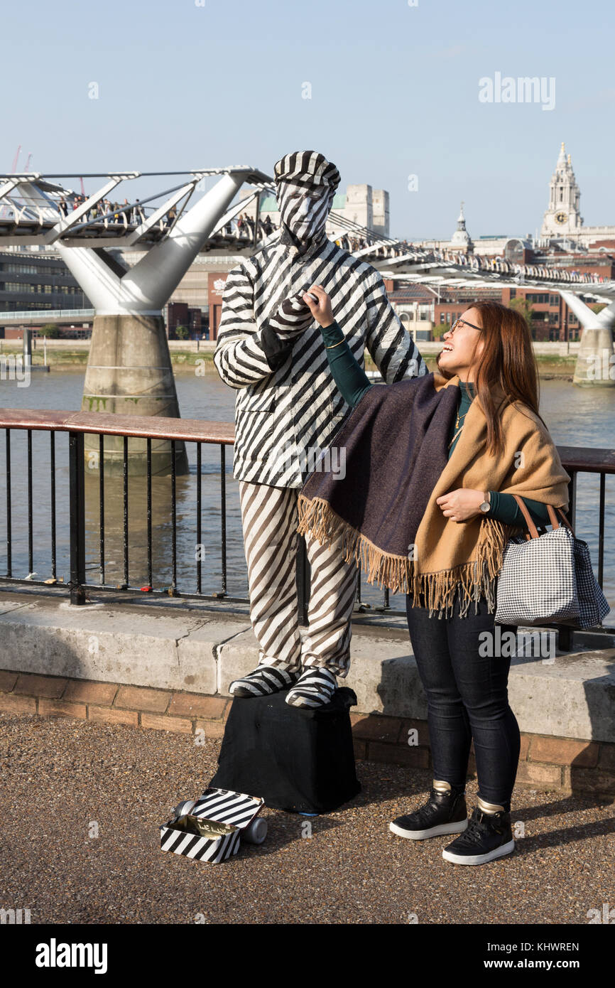 Human Statue in black and white stripes by Millennium Bridge, London, UK - Stock Image