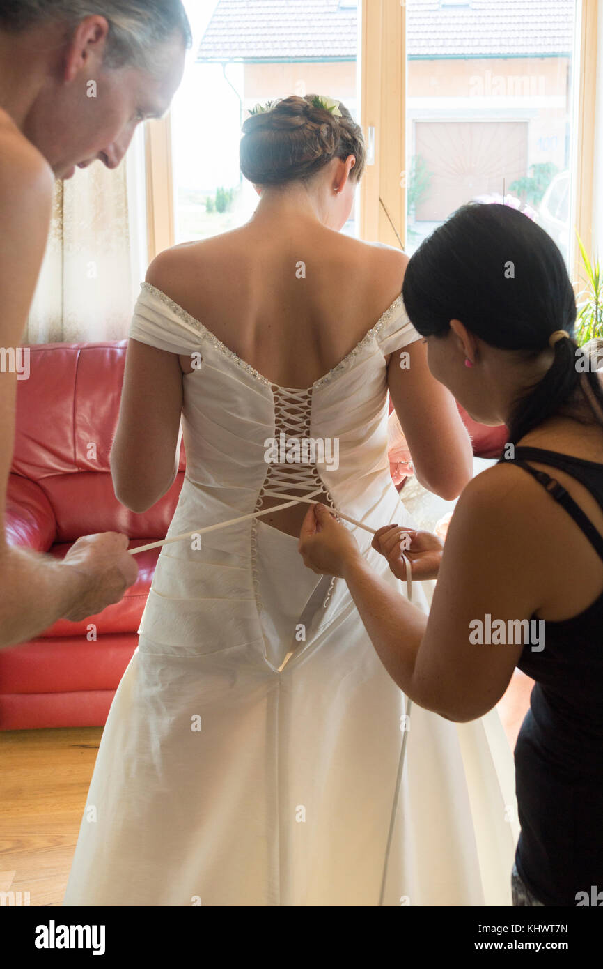 A young woman in her twenties being helped with her wedding dress by her father - Stock Image