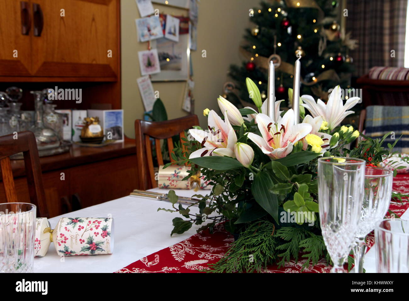 Beautiful floral centerpiece with candles on a festive dining table laid ready for Christmas Dinner in a traditional Stock Photo