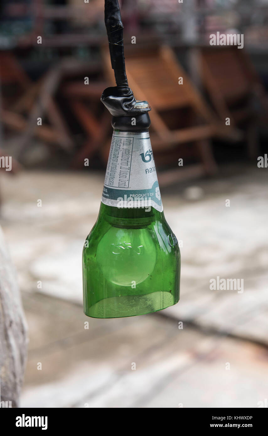 Beer bottle recycled as a hanging lamp in Thailand - Stock Image