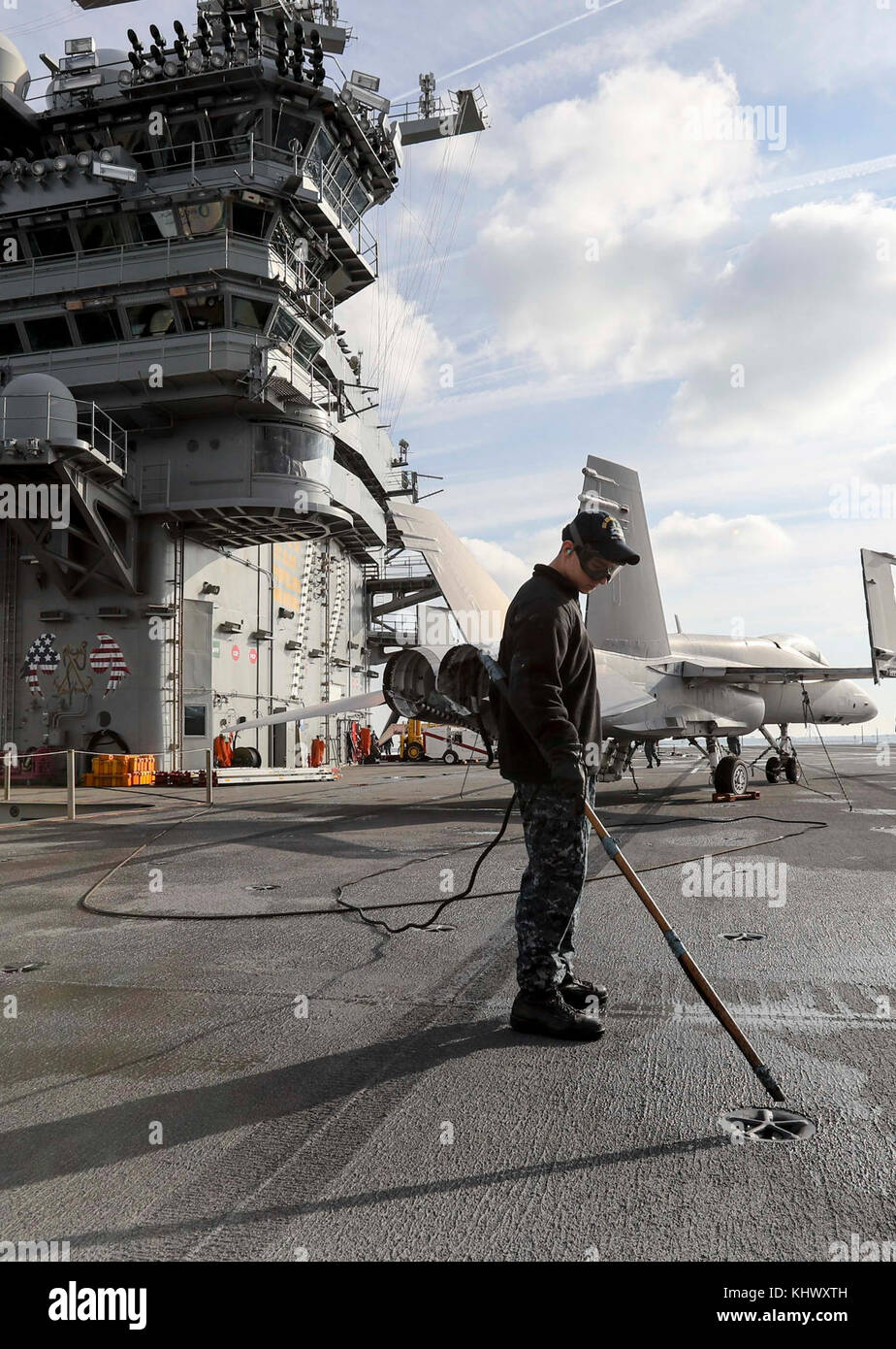 NORFOLK (Nov. 14, 2017) Airman Ryan Orfini removes debris from pad eyes on the flight deck of the Nimitz-class aircraft - Stock Image