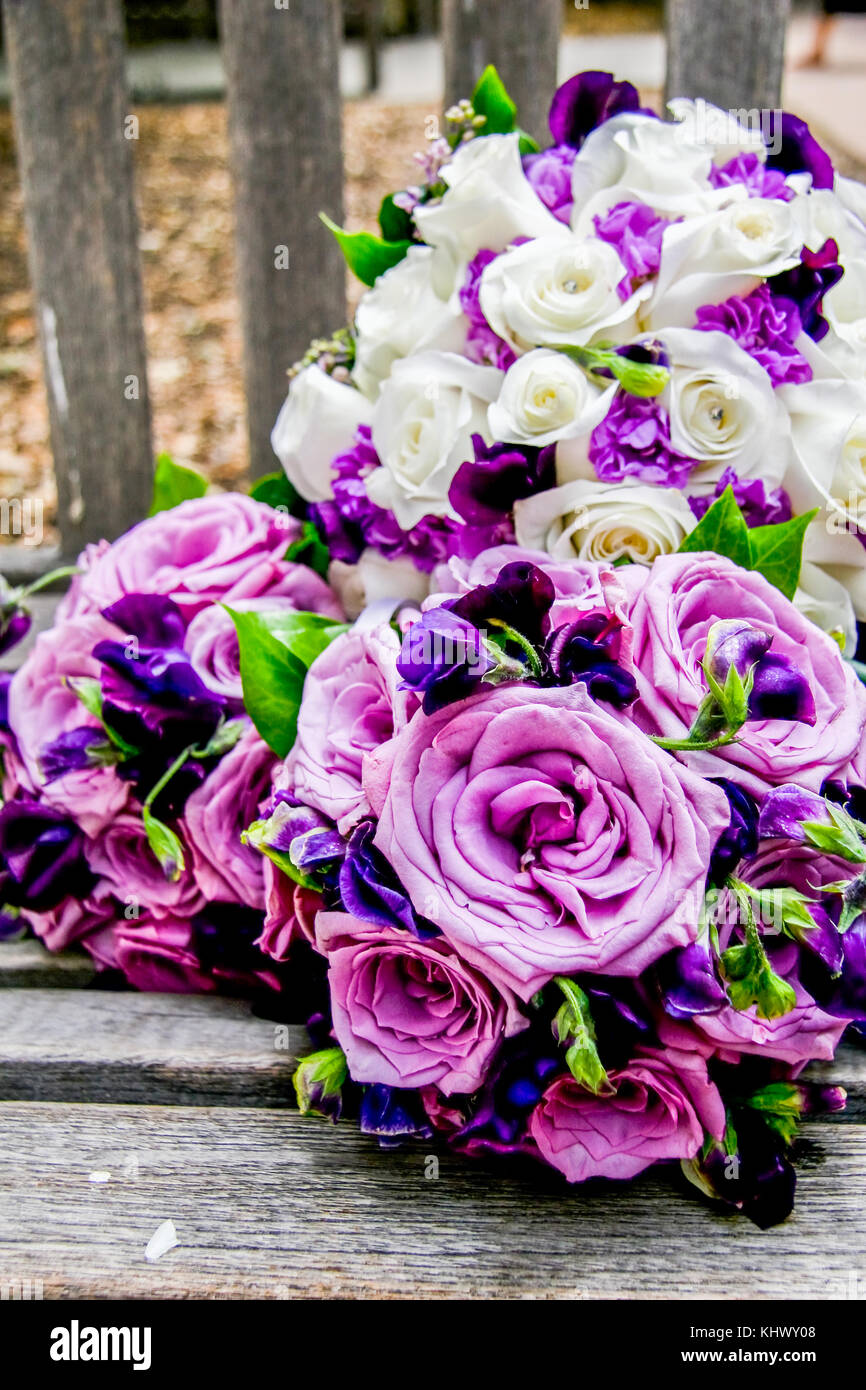A Purple And White Flowers Bridal Bouquet On A Wooden Chair In Park