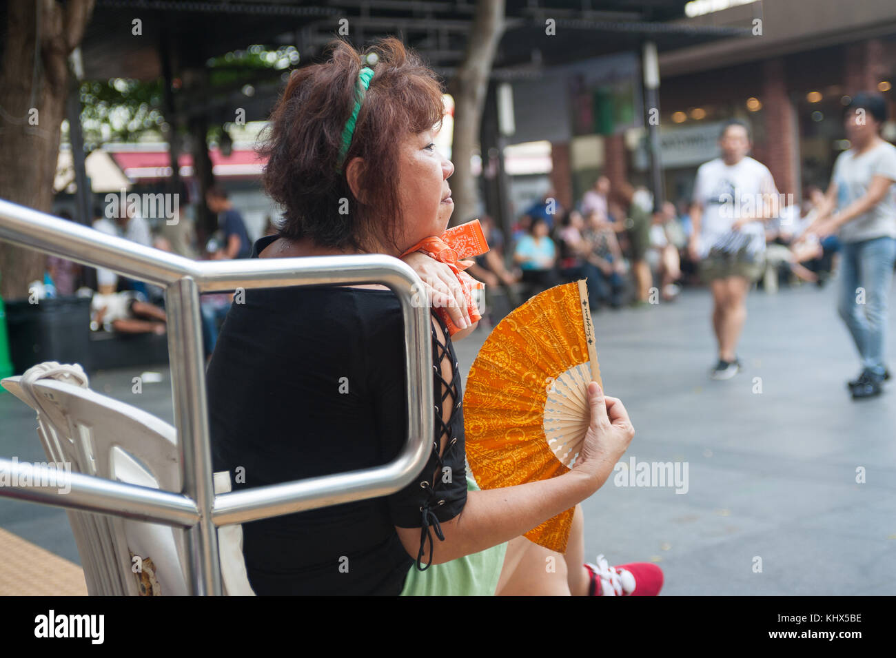 22.10.2017, Singapore, Republic of Singapore, Asia - A woman is seen fanning herself with a fan as she watches a - Stock Image