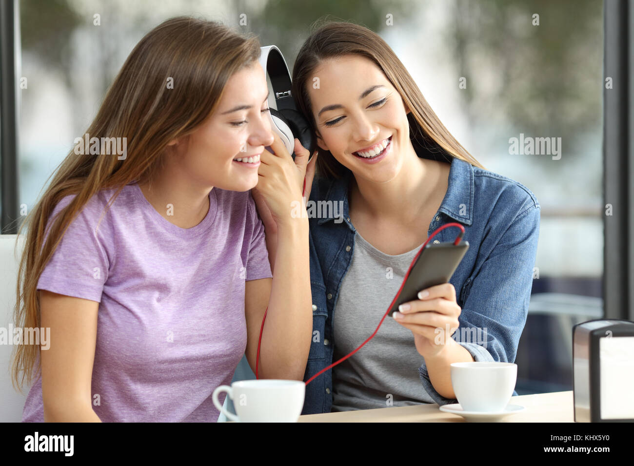 Two happy friends sharing on line music sitting in a bar - Stock Image