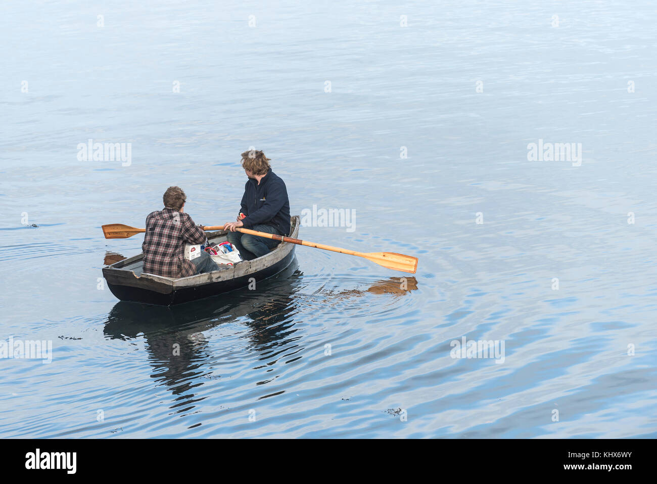 Two men people in a rowing boat. - Stock Image