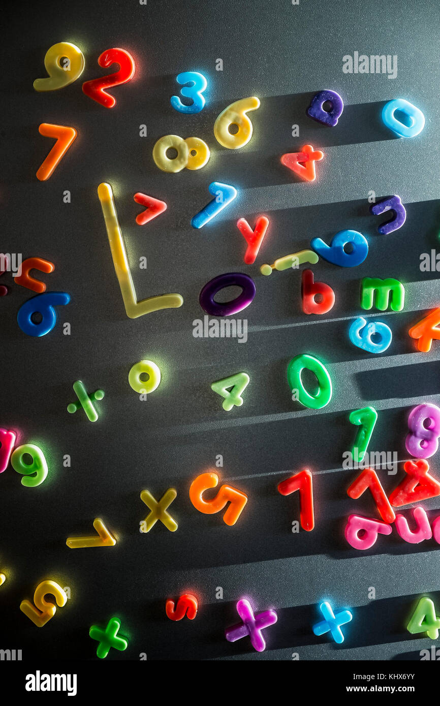 Colourful plastic magnetic letters and numbers stuck on a refrigerator door. - Stock Image