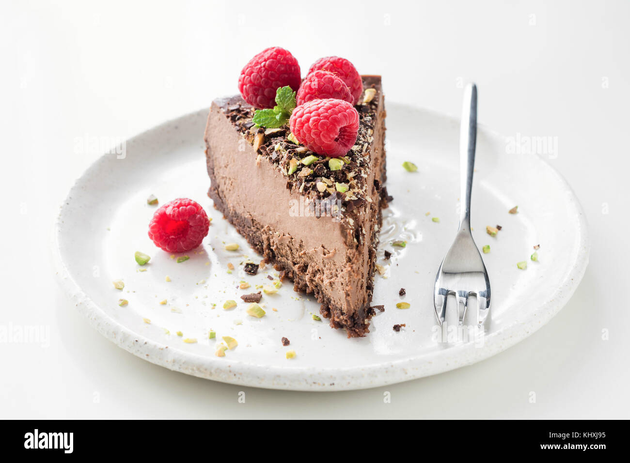 Slice of chocolate cake cheesecake decorated with crushed pistachio nuts, raspberries and mint leaf on white background. - Stock Image