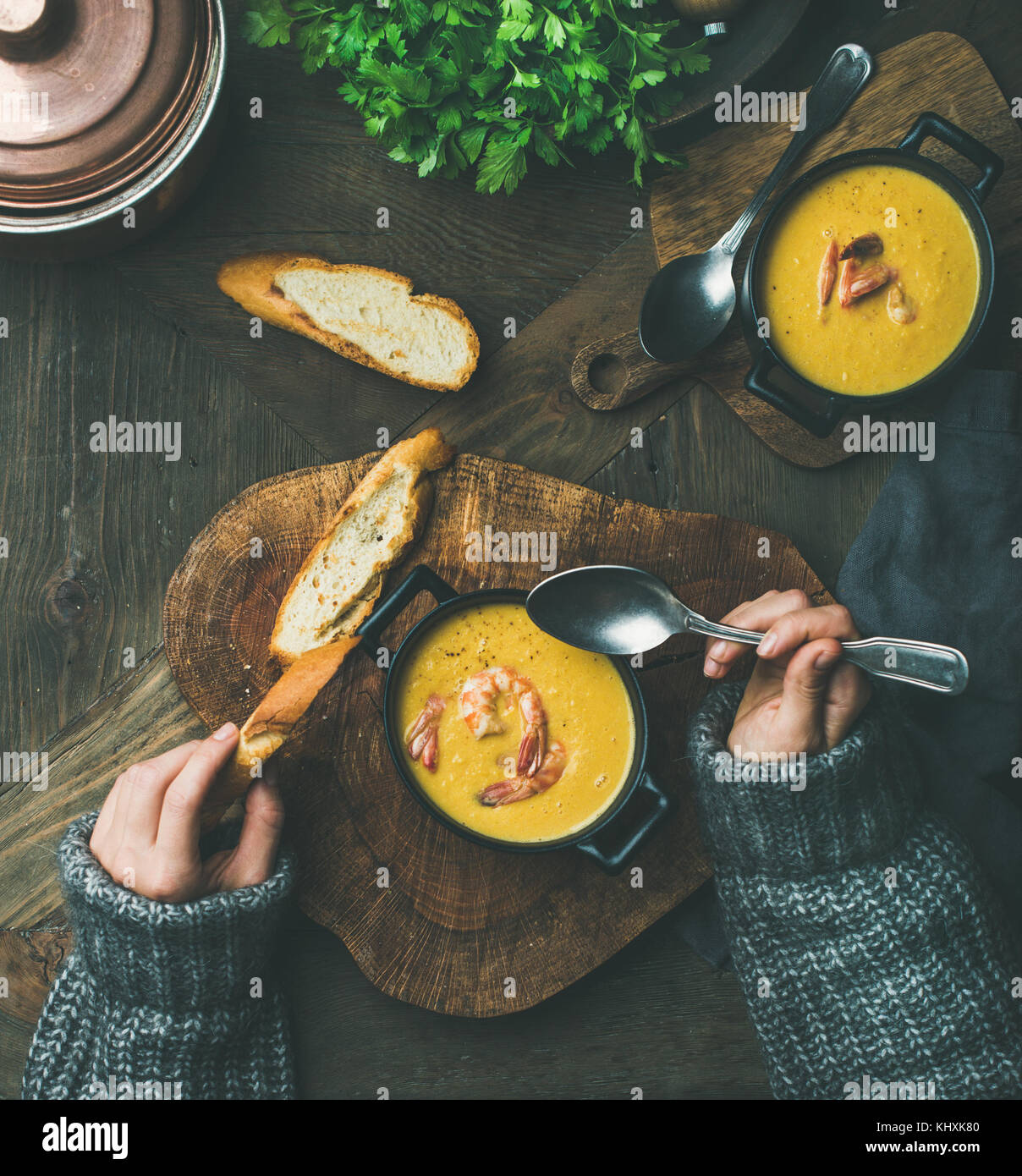 Woman in sweater eating corn creamy soup with shrimps - Stock Image