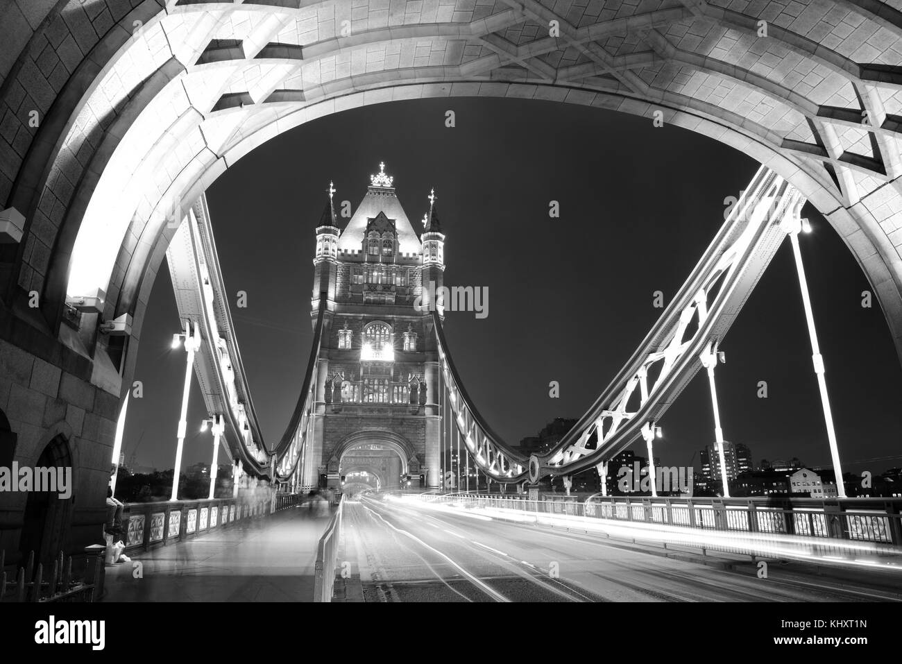 Tower Bridge in London with busy traffic at night. - Stock Image