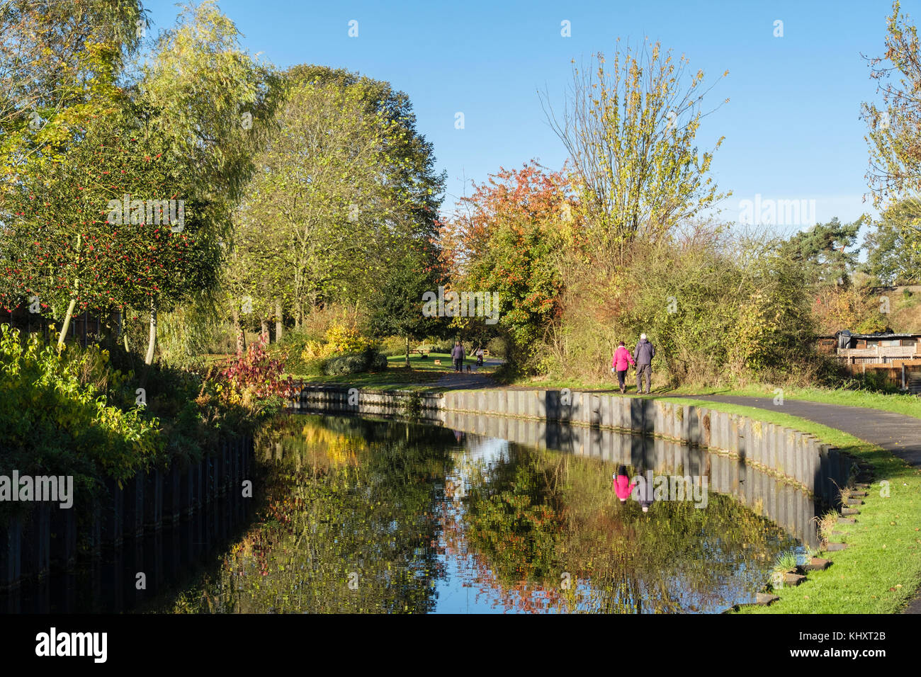 People walking on Droitwich canal towpath in Vines Park in autumn. Droitwich Spa, Worcestershire, England, UK, Britain Stock Photo