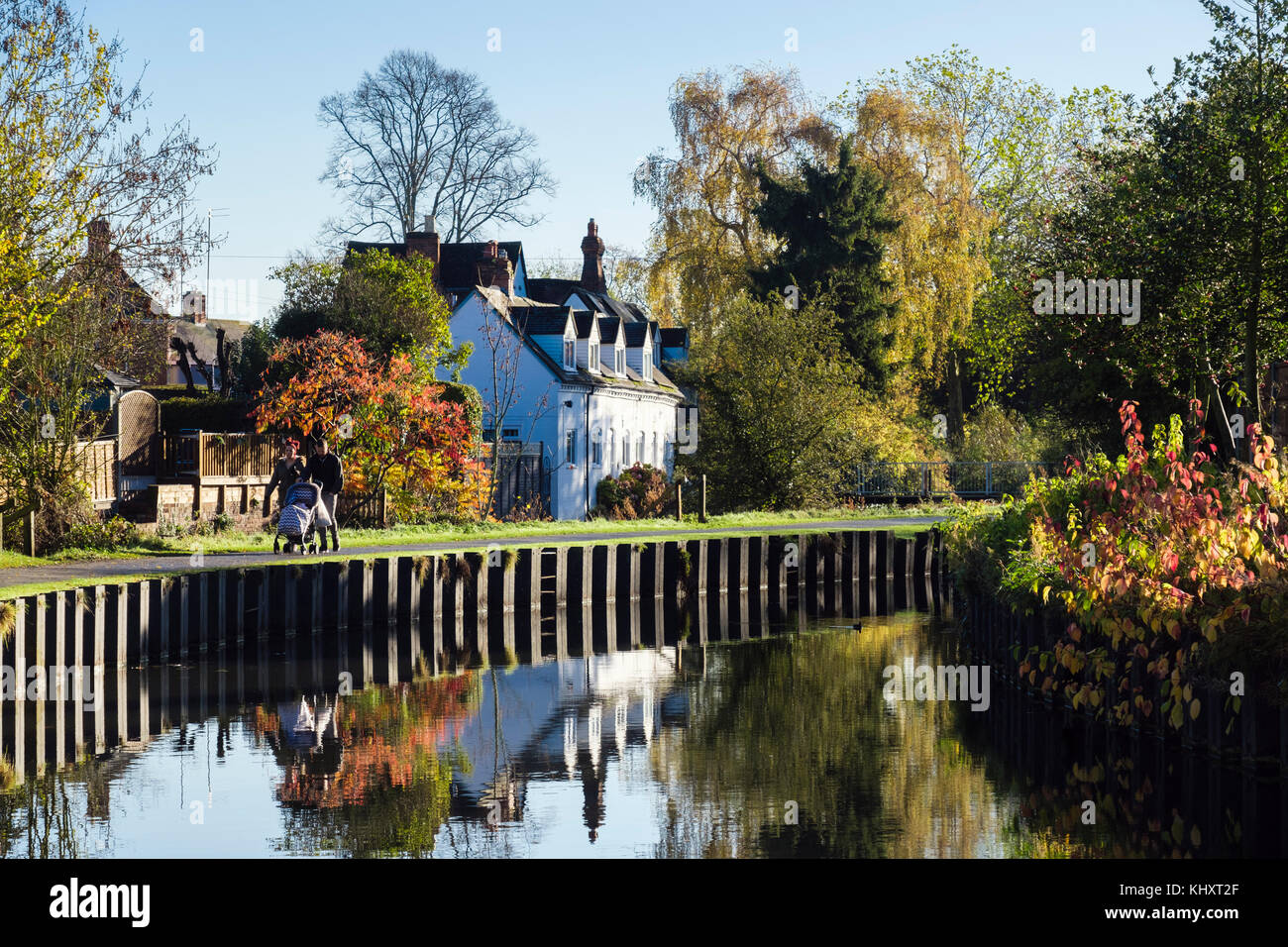 Couple pushing a pushchair walking on canal towpath in Vines Park in autumn. Droitwich Spa, Worcestershire, England, - Stock Image
