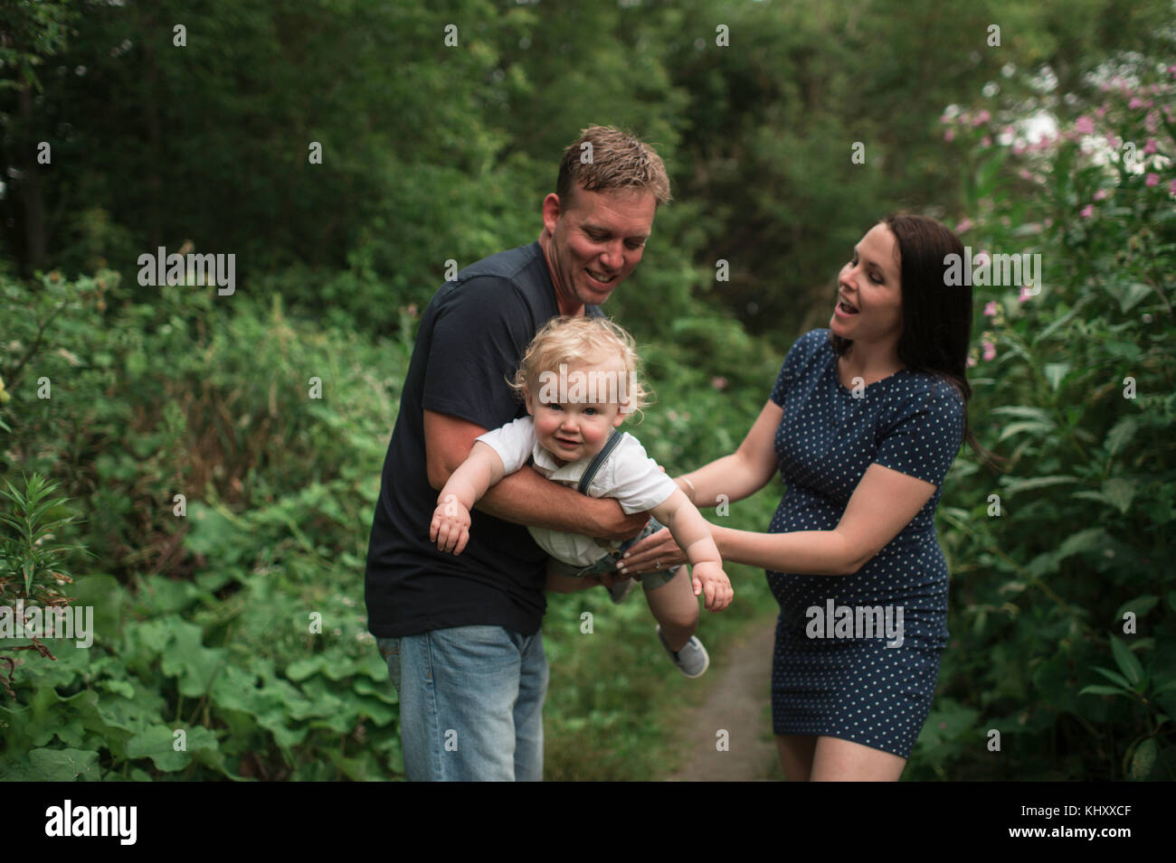 Pregnant couple swinging toddler son on pathway - Stock Image