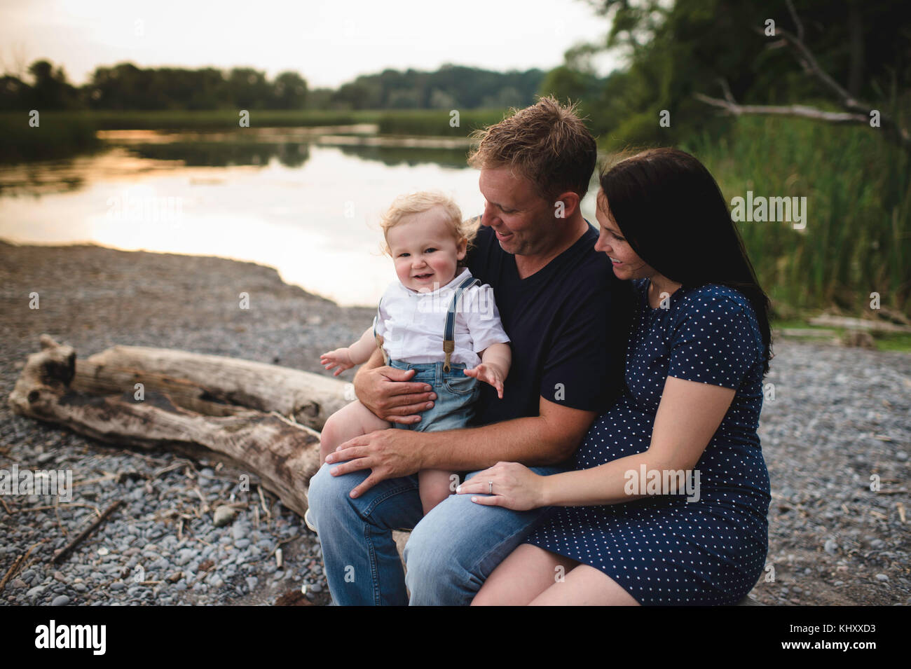 Pregnant couple sitting on beach log with male toddler son, Lake Ontario, Canada - Stock Image